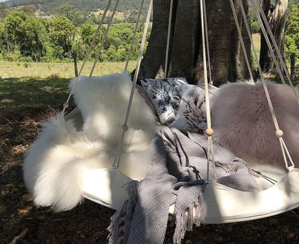 A circular swing with several fluffy cushions and throw blankets