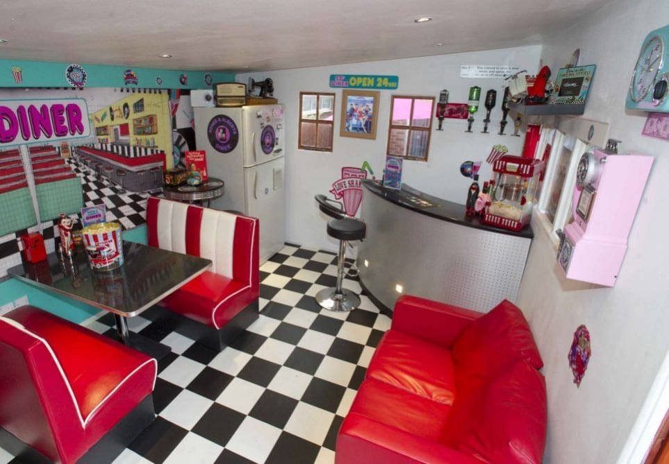 the interior of a shed made to look like a 1950's diner with red vinyl seats, a checkered floor and a corner bar
