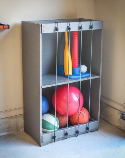 DIY crate storage with bungees across the front to keep toys in place