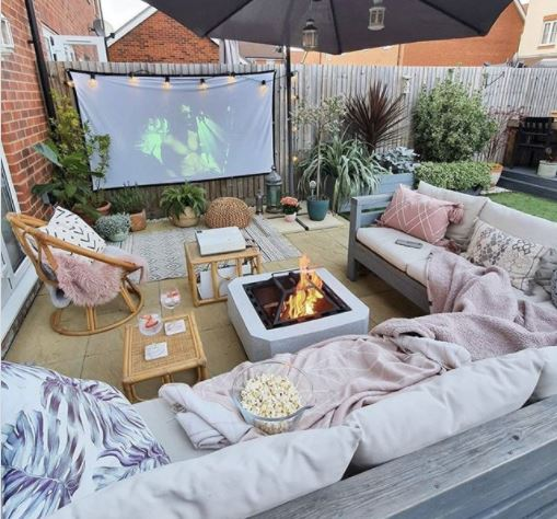 DIY garden cinema with a huge outdoor couch, fire pit and popcorn