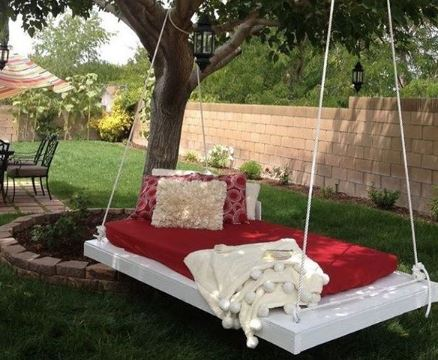 A DIY platform with a red futon and cream cushions hangs from a tree