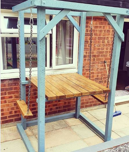 A blue wooden frame supports two narrow wooden swings facing a small dining table