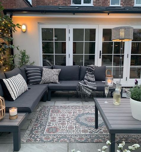 Dark slimline furniture on a patio with a rug, outdoor lamp and fairy lights
