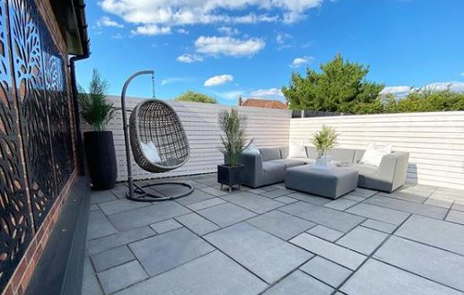 A grey swing chair sits in a minimalist garden with grey flagstones, white fence and grey garden sofas