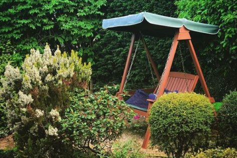 A traditional teak garden swing bench with canopy is tucked between hedges and shrubs