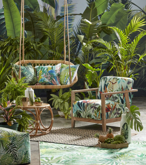 a swing bench and armchair in a tropical garden, both with cushions in a lurid leafy print