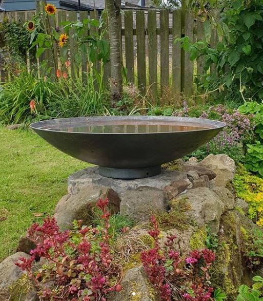 Japanese style water bowl on a stone plinth in a busy garden
