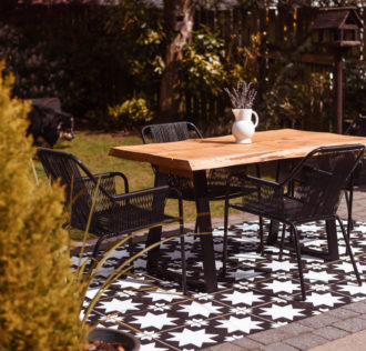 A patio that has been painted to look like black and white tiles