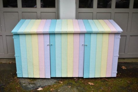 An outdoor bin store unit that's been painted in pastel rainbow shades to be used as toy storage