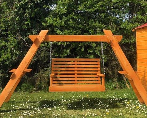 A sturdy swing bench made from orange-stained wood