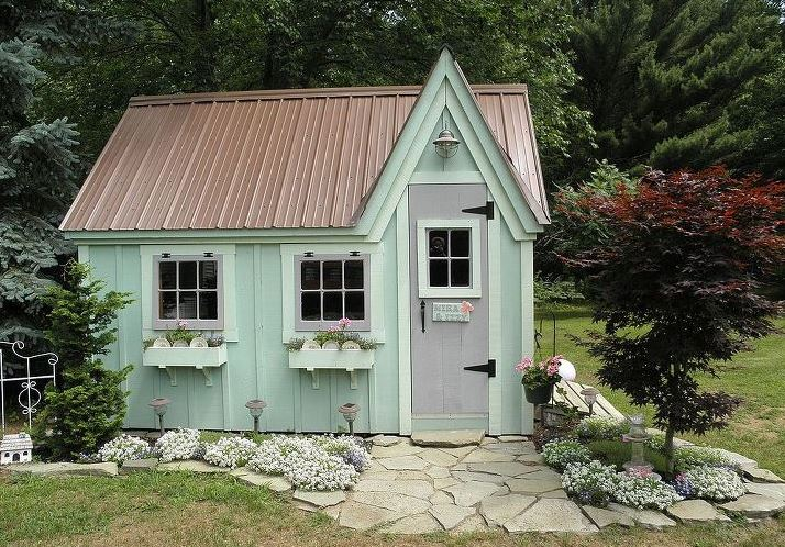 The exterior of a quaint garden shed, painted pale green, with a pitched roof and window boxes filled with flowers