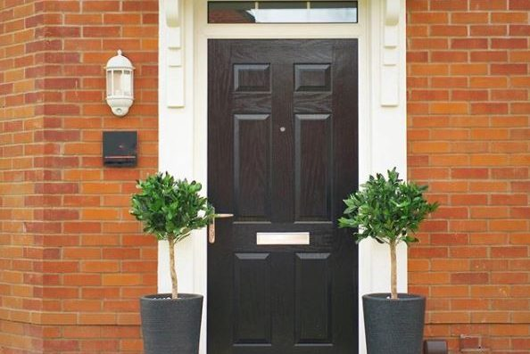 Two artificial bay trees stand either side of the front door to a new-build home, painted a smart black.