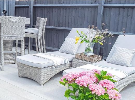 Two grey rattan loungers with grey blankets and cushions