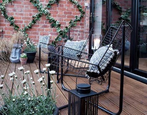 Two sleek wire chairs on a deck, surrounded by potted plants