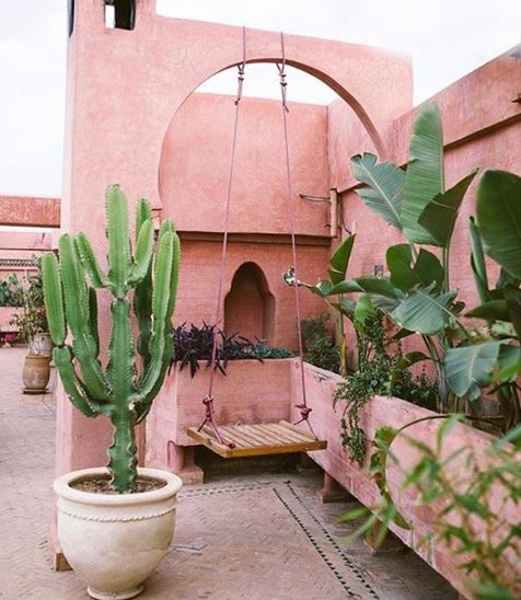 A simple wooden swing hanging from an archway in a moroccan inspired garden