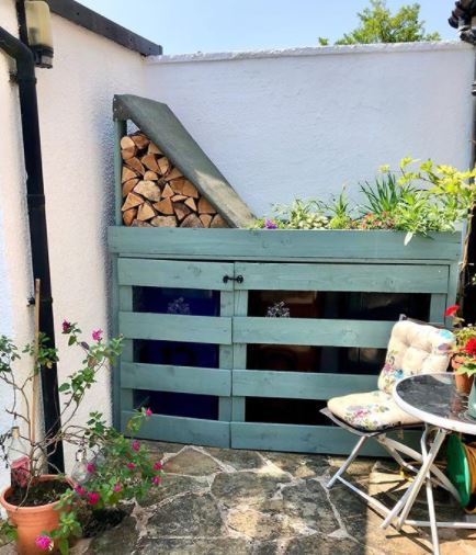 a DIY bin shelter with a small log store and green roof, and fits snugly in a garden nook.