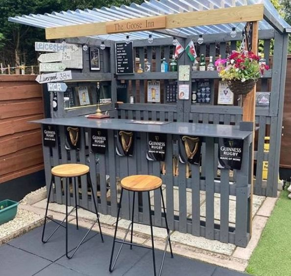 a DIY garden bar made from pallets with a clear plastic roof