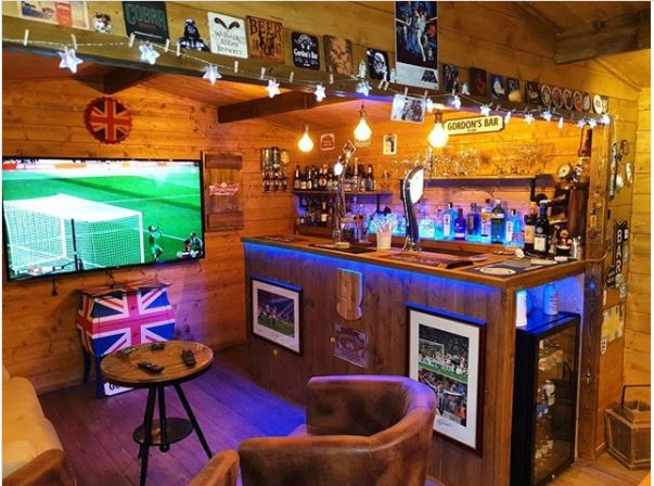 a DIY home bar, with pub-style counter, large TV and leather armchairs
