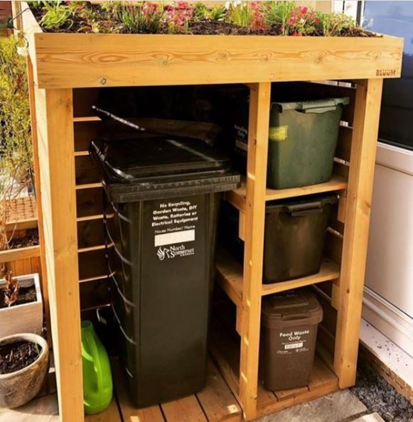 a bin shelter with a tall section for a wheelie bin and three shelves for recycling boxes