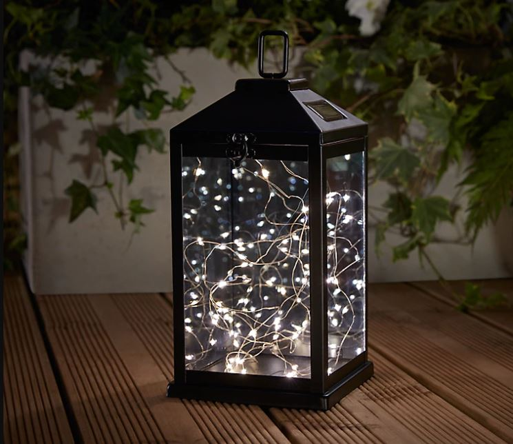 a black metal lantern filled with pretty fairy lights