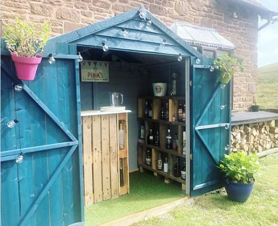 a blue garden shed with a pallet bar inside and alcohol bottles stacked on DIY shelving