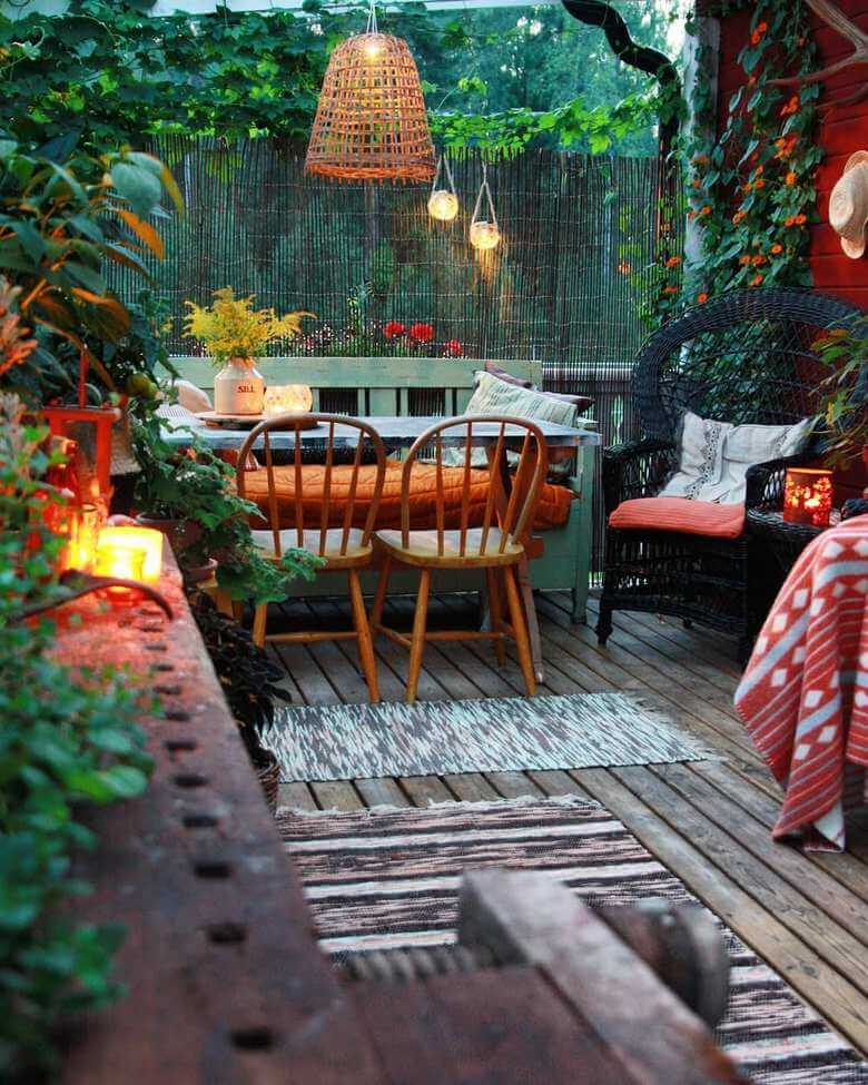 a boho style garden with a narrow table at the far end in front of a fence that lets you see the trees on the other side