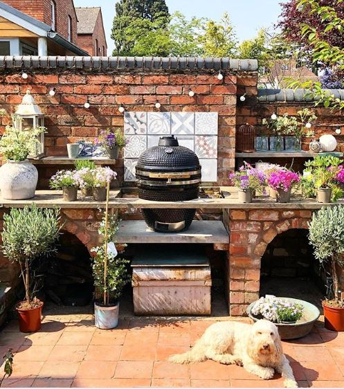 a patio with festoon lighting, potted plants and boho garden bbq area ideas