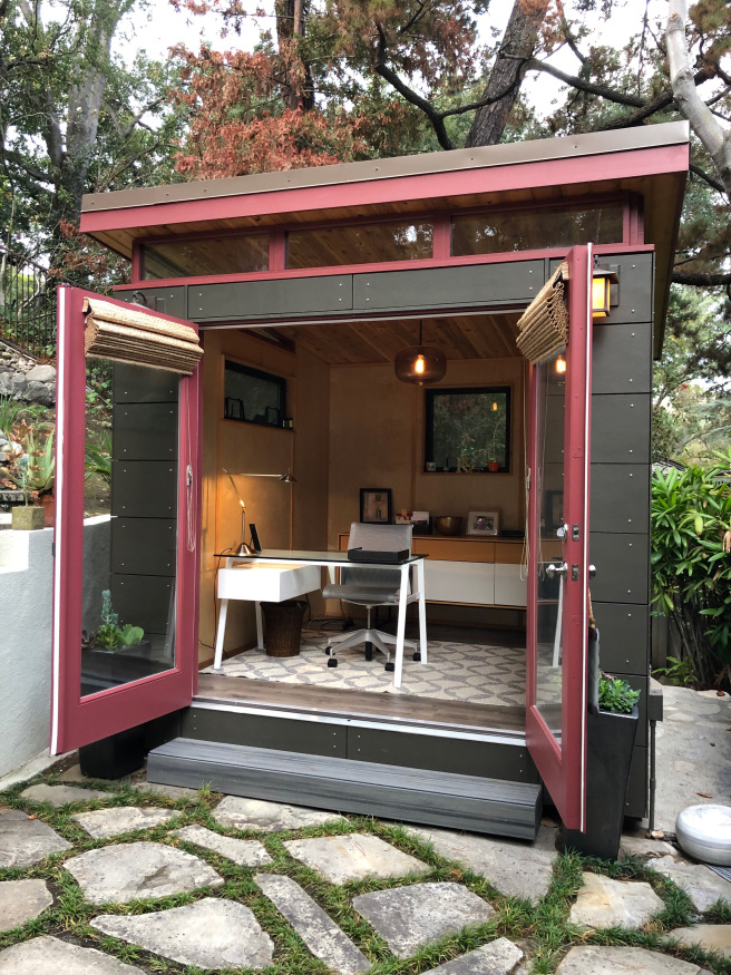 a boxy, modern shed with contemporary desk and shelving inside