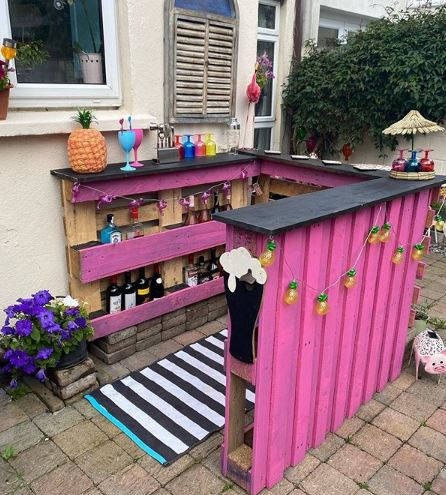 a bright pink pallet bar with multicoloured accessories like plastic wine glasses and novelty fairy lights