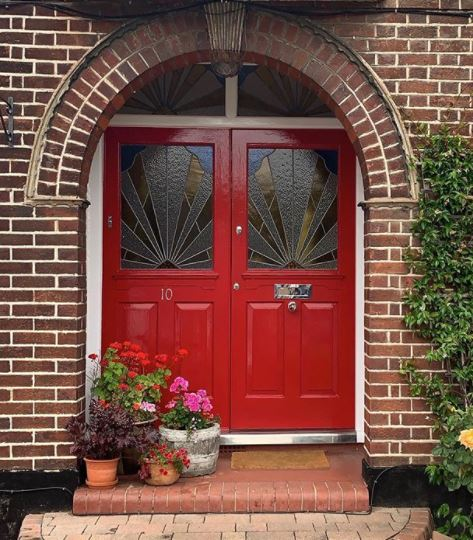 a bright red front door with shining hardware, and plant pots to one side