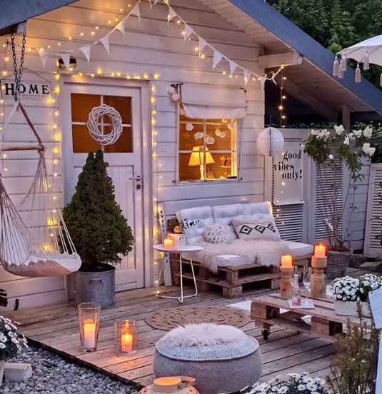 a busy deck outside a she shed, with pallet chair, pouffe, swing chair, bunting and candles, all in shades of cream and pale grey
