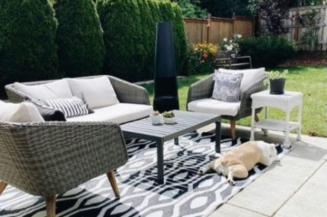a concrete patio with an outdoor rug and patio furniture