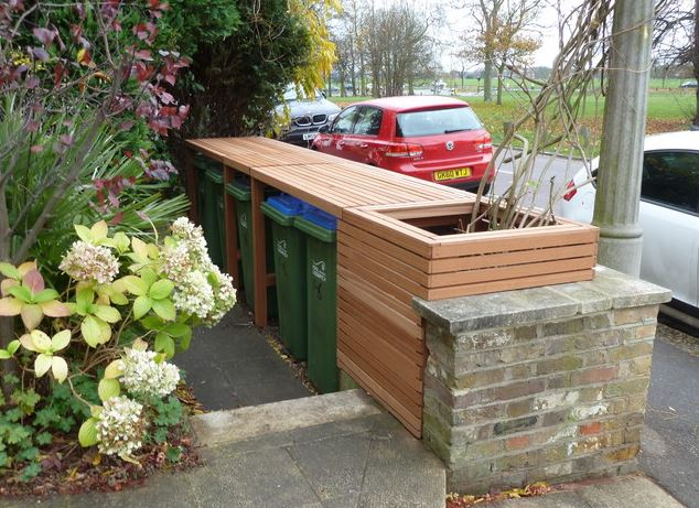 a contemporary bin store positioned so it's flush with the front garden wall