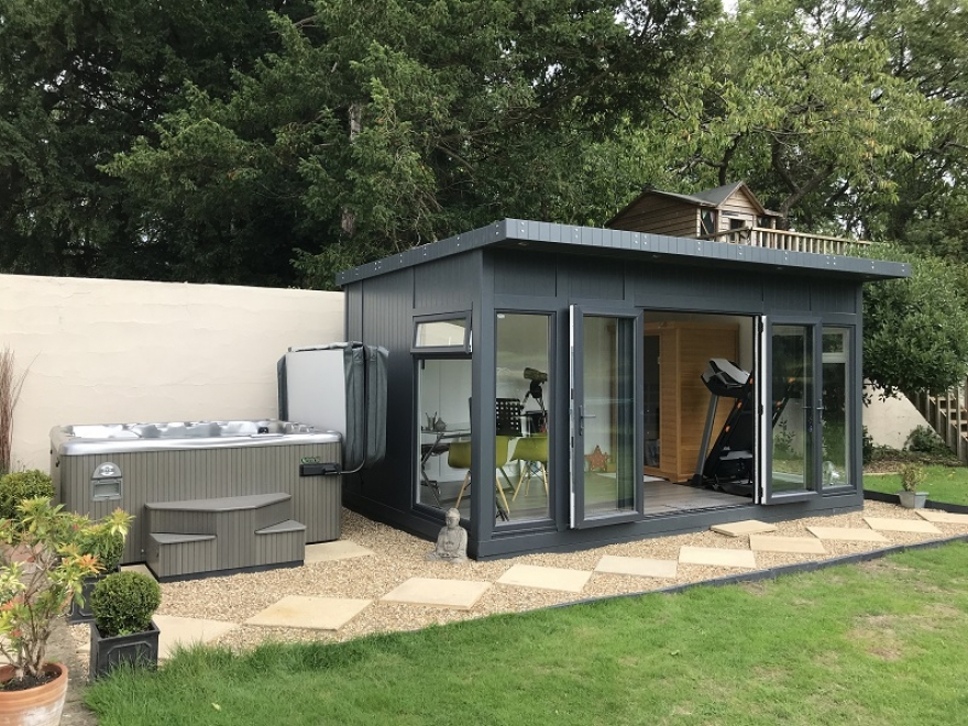 a contemporary garden man cave with desk, treadmill and storage cupboard inside, and a covered hot tub area outside