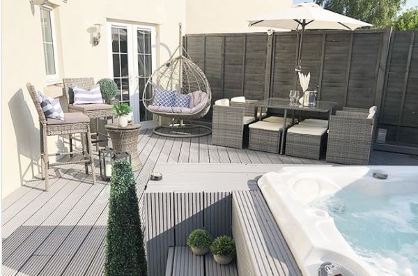 a contemporary grey deck with rattan furniture, hanging chair and hot tub sunk into a raised deck