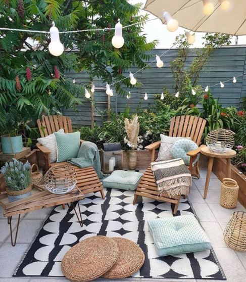 a cosy patio with seating and cushions with string lights zig-zagging across