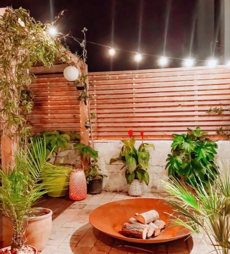 a courtyard garden with potted plants, wooden fencing and a large fire bowl