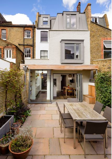 a courtyard with subtle rectangular shapes in the table, chairs, paving stones, fencing, planter and architecture.