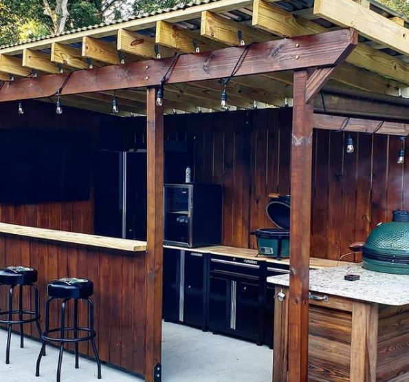 a covered patio area with outdoor kitchen appliances and a bar counter with stools