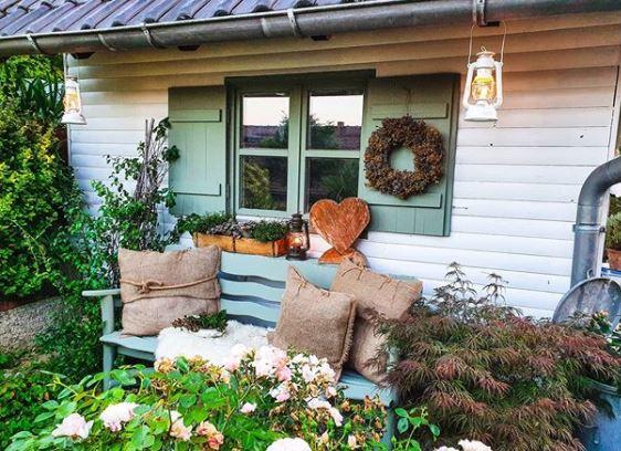 a cute garden bench beneath a shuttered window, both painted sage green
