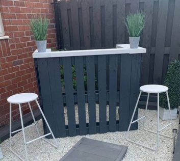 a dark grey pallet bar with white countertop and white stools, on a pale gravel patio