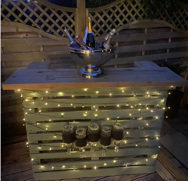 a deck with a pallet bar that has fairy lights strung around it