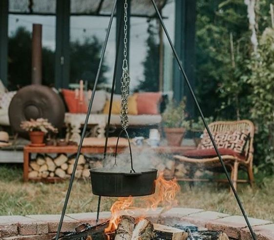 a fire pit with a pot cooking on a tripod over a flame