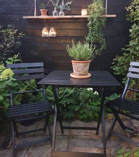 a fold-up set of table and chairs in matte black, on a leafy patio