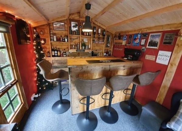 a garden shed transformed into a home pub, with bar stools and fully stocked drinks shelves