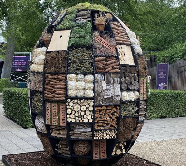 a giant, egg-shaped insect hotel with many compartments, filled with different garden materials