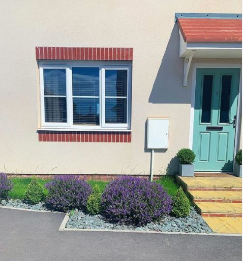 a gravel front garden with blue stones, similar to the front door. The electrical box is a similar colour to the cream walls.