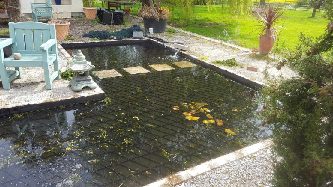 a large garden pond with a solid safety mesh just beneath the surface of the water