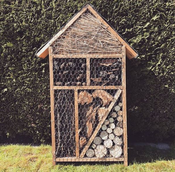 a large insect hotel with compartments for logs, sticks, pine cones and hay