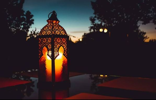 a moroccan lantern with a burning candle inside, on a table, at dusk